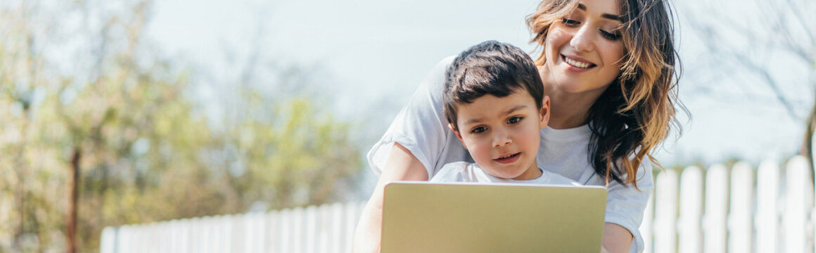 horizontal concept of happy mother and son using laptop outside