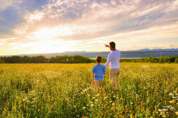 happy family of father and child on field at the sunset having fun pointing something