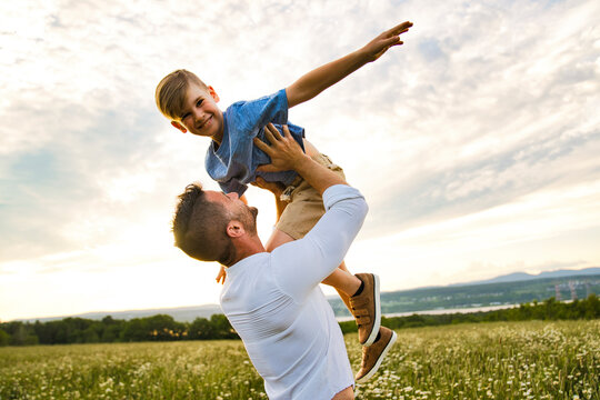 happy family of father and child on field at the sunset having fun flying in the air
