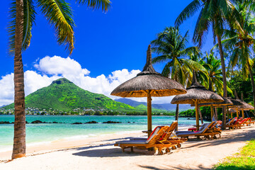 Relaxing holidays in tropical paradise. Mauritius island. Flic en Flac beach, view of Tamarin mountain
