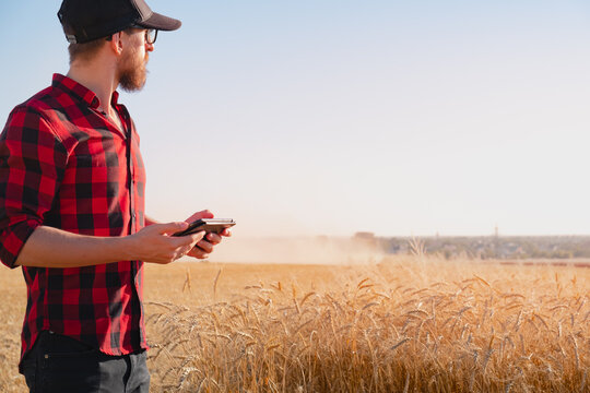 Millennial man with a tablet in a dusty agricultural field. Modern farming, agriculture business, harvest management