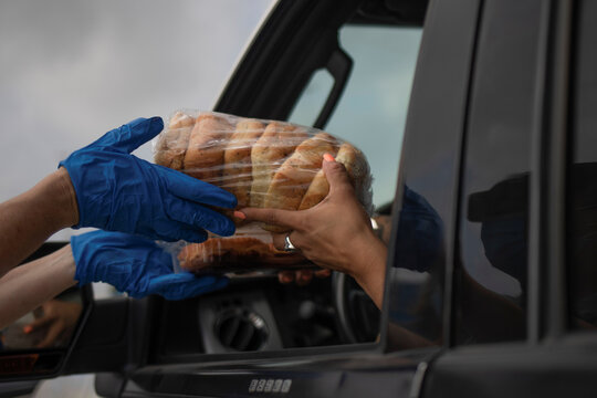 Volunteer hands bread to resident economically affected by COVID 19 pandemic during San Antonio Food Bank distribution in Texas