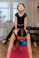 Woman doing fitness exercises with children at home.