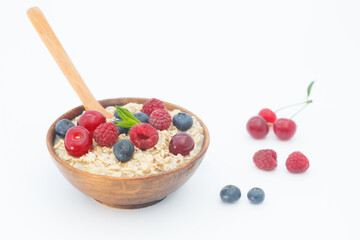 Rolled oats with blueberries and raspberries on white background. Healthy breakfast cereal oat flakes in wooden bowl with wooden spoon.