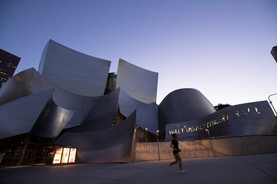 A person wearing a face mask jogs by Walt Disney Concert Hall at dusk during the outbreak of the coronavirus disease (COVID-19), in Los Angeles