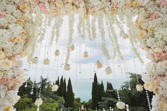 Wedding arch with flowers and beads on blue sky background close-up.