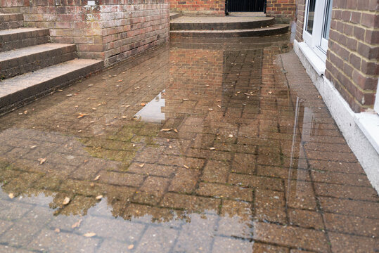 Brick patio area flooded after heavy rain due to a blocked soakaway