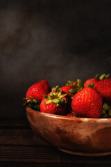 Still life of a bowl full of fresh picked strawberries on a wood table. Vertical format with copy space. Light painting technique.