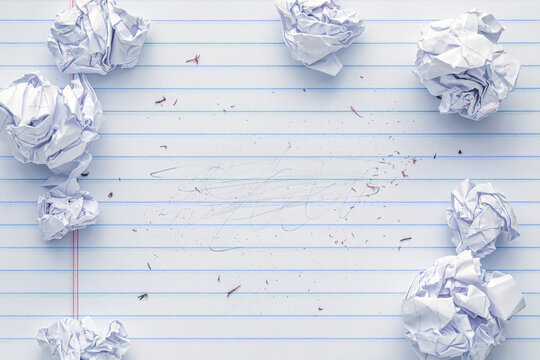 School supplies of blank lined notebook paper with eraser marks and erased pencil writing, surrounded by more trashed balled up paper. Studying or writing mistakes concept.