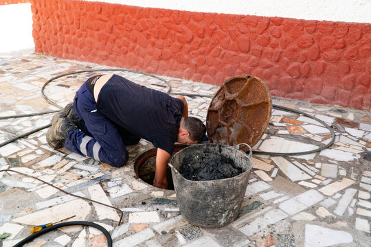 Worker cleans the drains hatch and removes dirt and debris from the sewer. Plumber cleans the sewer