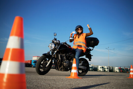 Motorcycle driving school. Student showing motorcycle driving license as successfully finished riding lessons.