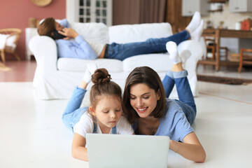 Aluminium Prints Akt Happy mom and little child girl looking at screen laptop, talking to webcam, chatting online via computer app.