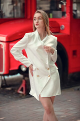 young woman near english bus. London red bus - girl enjoying life. portrait of Beautiful femail model wearing at white long jaket.