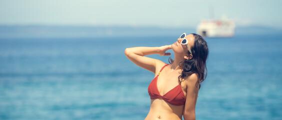 Beautiful young woman sunbathing at the seaside in red bikini