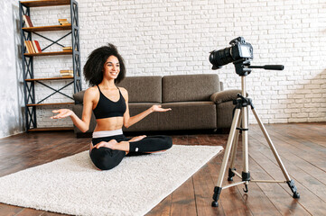 Young sporty slim mixed-race woman yoga coach records video online training yoga. An african-American girl sits in lotus pose and looks into camera in front of her and explains something