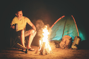 Tourist is sitting near campfire and is drinking a tea from a cup.