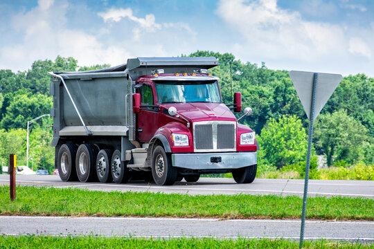 Large Dump Truck Delivering Gravel To Commercial Construction Site
