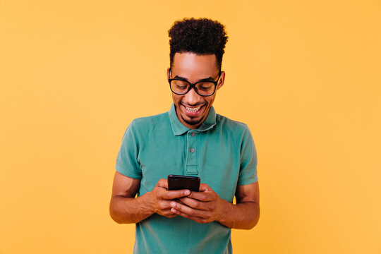 Handsome black guy in big glasses reading phone message. Studio portrait of pleased african man holding smartphone.