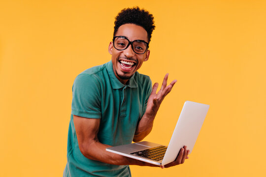 Handsome male freelancer in glasses smiling on yellow background. Ecstatic african student holding laptop and expressing happiness.