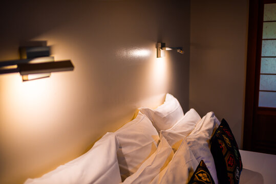 Modern contemporary new Japanese house ryokan hotel bedroom room with two mounted to wall reading lamps lights and pillows on white clean made bed