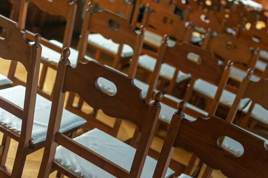 many empty wooden chairs in the audience
