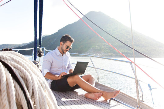 Man working on yacht office with laptop. Traveling on sailboat. Traveler using tablet computer. Freelancer workplace in self isolation, social distance. Successful business lifestyle.