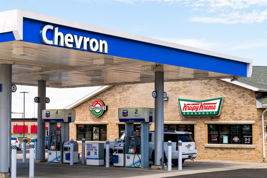 Spanish Fork, USA - July 29, 2019: Krispy Kreme doughnuts fast food donut chain business facade exterior entrance sign in Utah by Chevron gas station pump