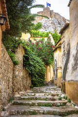 Fototapete - Plaka district in Athens, Greece. Narrow street with vintage stairs and old houses, traditional alley overlooking famous Acropolis of Athens.