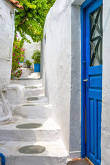 Fototapete - Old blue door on narrow street in Anafiotika, Plaka district, Athens, Greece. Plaka is tourist attraction of Athens. Vintage alley with stairs