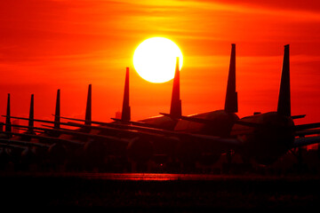 airplanes at airport apron with beautiful sunset background