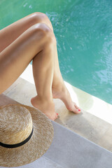 Young woman enjoying a hot summer day near swimming pool. Women's legs close up. Relaxation and wellbeing concept.
