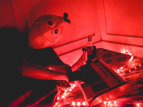 Bizarre portrait of a guy with lemon mask on a old mattress playing the keyboard, with neon red lights