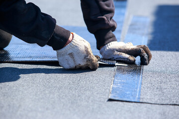 Worker cuts roofing material