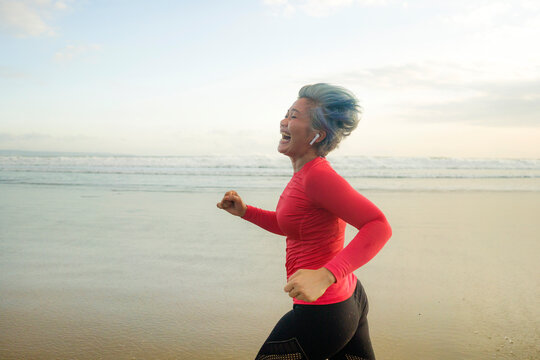 fit and happy middle aged woman running on the beach - 40s or 50s attractive mature lady with grey hair doing jogging workout enjoying fitness and healthy lifestyle