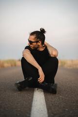Hombre joven con gafas de sol negras, ropa negra, botas negras y moño sentado en mitad de la carretera