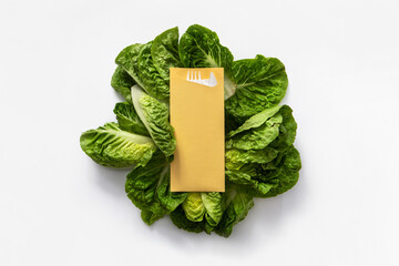 mustard yellow take away cuttlery pouch on lettuce leaves