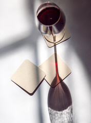 glass of red wine with coasters under the sun shadow