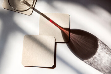 shadow of a glass of red wine with coasters under the sun