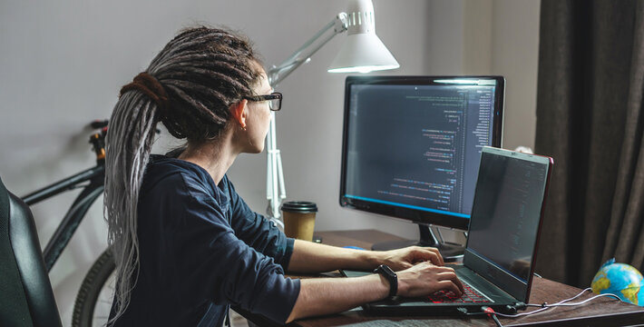 Modern young female programmer is writing program code on a laptop at home. The concept of software development.