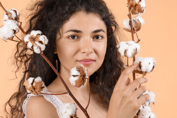Beautiful young woman with cotton flowers on color background