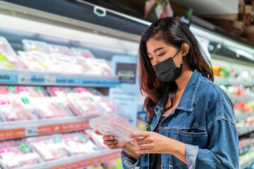 Young Asian woman wearing protective face covering choosing food in shop