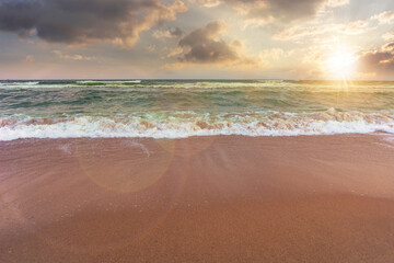 sandy beach and turquoise sea at sunset. great view of waves rolling to the coastline. wonderful weather with glowing sky in evening light