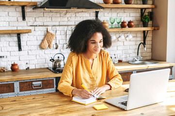 Pleasant afro-american girl sits in front of the laptop and she is writing down something in her notebook. She sits at the kitchen table. Online courses