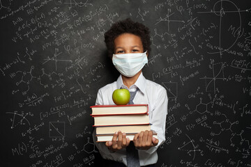 Photo sur Toile Les Textures Happy child in medical protective face mask holding books and green apple on blackboard background