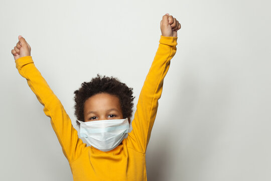 Portrait of happy black child boy in medical protective face mask holding hands up