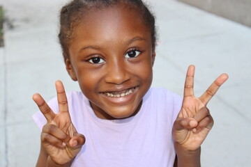 Close up of young child holding up peace signs with both hands