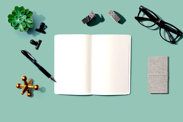 Notebook with office supplies and a plant - flat lay