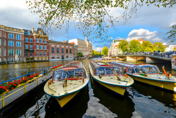 Colorful yellow and red tour boats wait in a line for tourist passengers on a major canal in Amsterdam, Netherlands