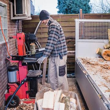 Man cutting firewood with wood splitter