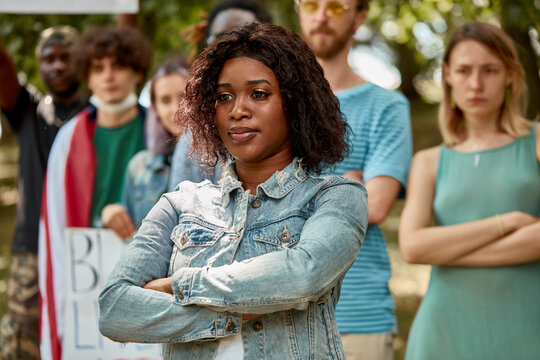 serious black female ready to stand her rights, woman protests outdoors. group of diverse youth stand in the background. black lives matter
